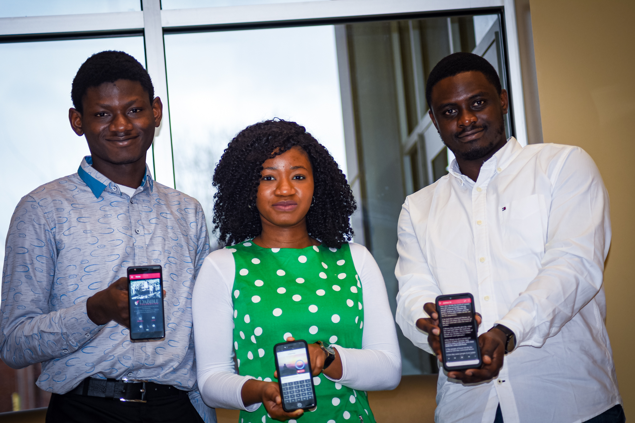 Users holding our bible app - dabible foundation